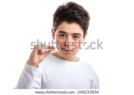 smooth-skinned Caucasian young boy in a white long sleeve t-shirt making pinching gesture with the thumb and index finger - stock photo