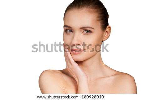 Smooth touch. Beautiful young shirtless woman touching her cheek and looking at camera while isolated on white background - stock photo