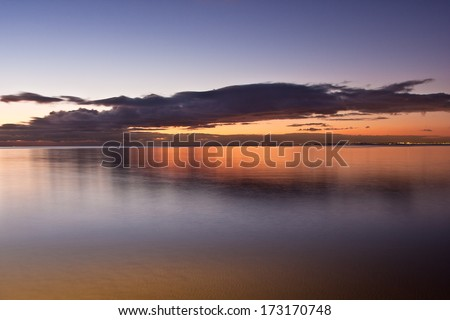 Smooth water surface in orange sunset  colors with city of melbourne lights shining in the distance - stock photo