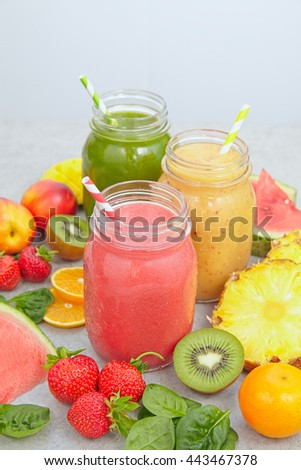 Smoothie jars surrounded by sliced fruits and berries - stock photo