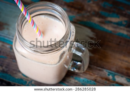 Smoothie milkshake made from peach,melon and papaya blended with kefir yogurt. Served in a jug style glass on a rustic wooden table with a colorful stripy straw. - stock photo