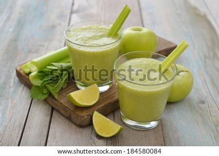 Smoothie of green apple, celery, avocado and lime on wooden background - stock photo