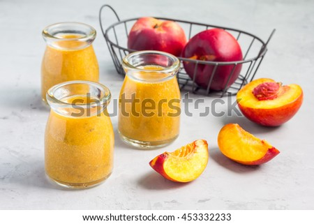 Smoothie with nectarine, orange juice, chia seeds and honey, in glass jar, horizontal, concrete background