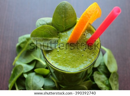 Smoothie with spinach leafs and sliced orange - stock photo