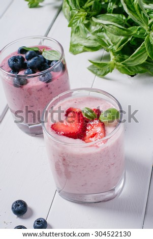 Smoothie with strawberries and blueberries in a glass on a white wooden background with basil - stock photo