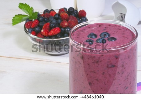 Smoothie with wild berries (blueberry, wild strawberry) and ingredients for it.  Close-up