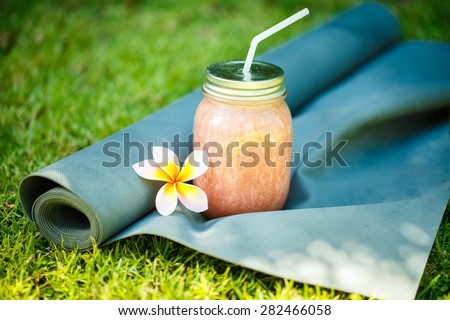 Smoothies and yoga mat on the grass - stock photo