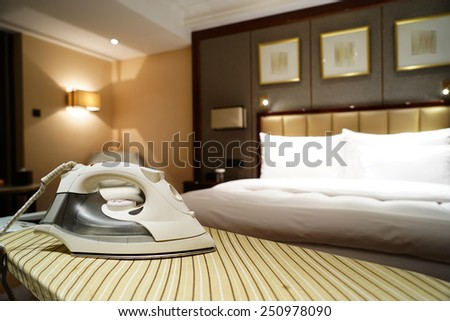 Smoothing-iron on an ironing board in hotel room - stock photo