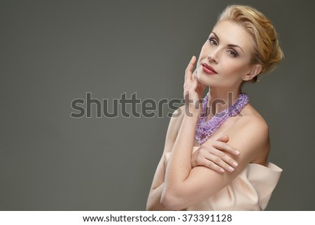 Smoothness you can see. Horizontal studio shot of a gorgeous elegant mature female posing touching her face looking to the camera softly - stock photo