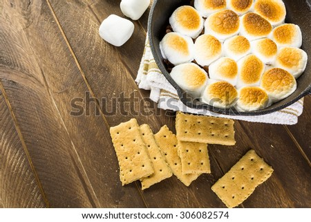 Smores dip prepared with large marshmallows in cast iron pan.