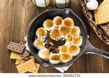 Smores dip prepared with large marshmallows in cast iron pan. - stock photo