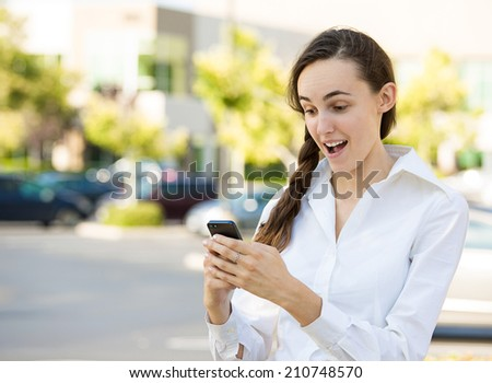 SMS. Portrait funny young businesswoman reading news, text message. Beautiful young caucasian woman isolated outdoor street background holding her smart phone. Human face expression, emotion, reaction - stock photo