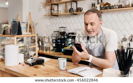 Sms. Smiling and positive male barista sending messages using smart phone while drinking coffee and making some notes being at work during his break