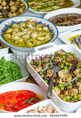Snack bar - paprika, artichokes, zucchini , olives , tomatoes , arugula , garlic . Healthy , natural and healthy Italian and Mediterranean food. Close-up on the table.