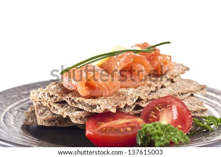 snack from a salmon with crispbread, vegetables and a lemon