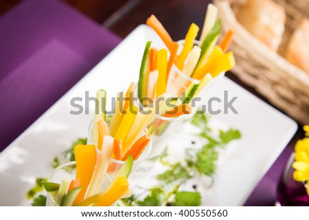 snack from cucumber,carrot,pepper on white dish in restaurant - stock photo