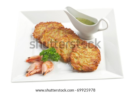 Snack from the fried potato flat cakes, boiled shrimps and sauce on a light plate. A shot horizontal, focus in the shot center - stock photo
