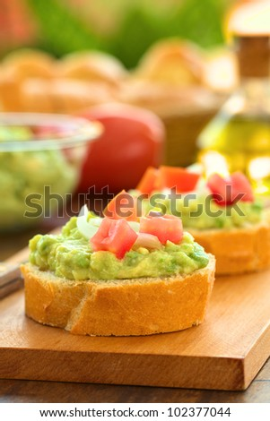 Snack of baguette slices with avocado cream, tomato, onion on wooden cutting board with ingredients in the back (Selective Focus, Focus on the front of the avocado cream on the first baguette slice) - stock photo