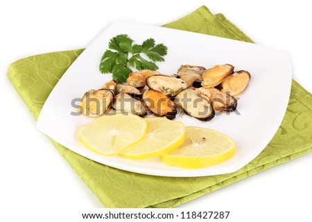 Snack of mussels and lemon on plate isolated on white