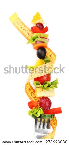 Snack of vegetables on fork with measuring tape isolated on white - stock photo