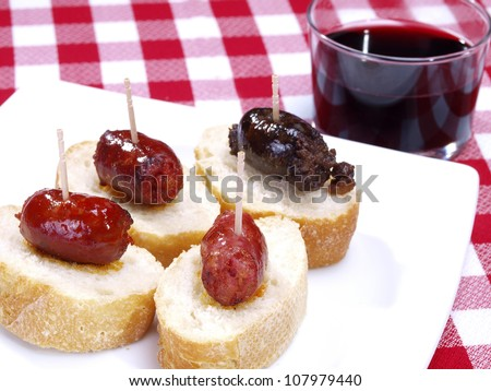 Snack Size Sausages. Assortment of snack size sausages with red spicy sausages, black onion sausages and white meat sausages. Typical size for Spanish Tapas. - stock photo