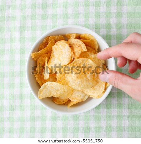 Snacking from the potato chips bowl - stock photo