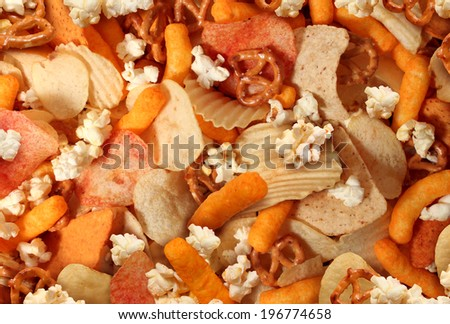 Snacks background with salty crunchy treats as potato chips and cheese flavored puffs fried or baked food as pretzels pop corn and nachos as a symbol of assorted party mix appetizer. - stock photo