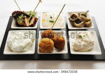 snacks like octopus,fish,croquettes balls and different kind of sauces on a plate on a close up - stock photo