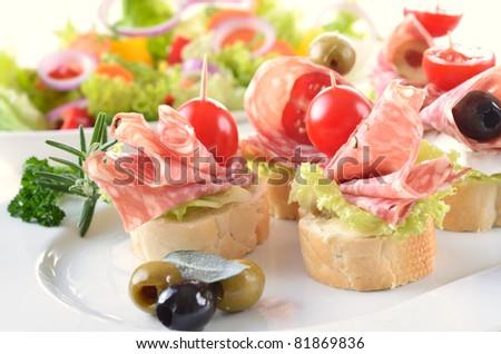 Snacks with Italian salami and ripe cherry tomatoes - stock photo