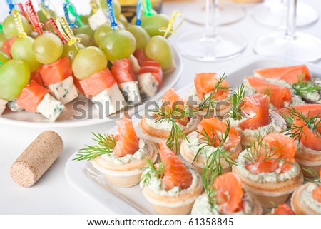 Snacks with salty salmon, cheese and grapes for wine - stock photo