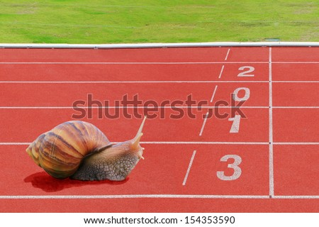 Snail effort running on red rubber track  near finish line with numbering year 2013. - stock photo