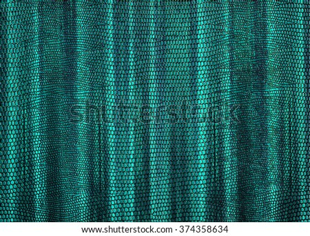 Snakeskin print curtain in blue green for use as a background or texture - stock photo