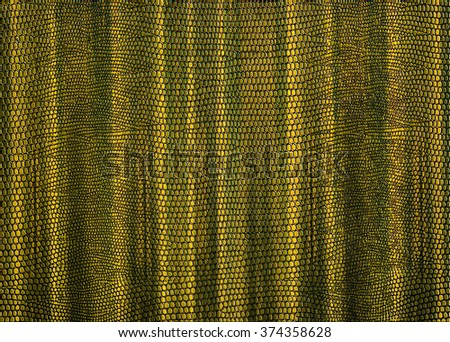 Snakeskin print curtain in gold for use as a background or texture - stock photo