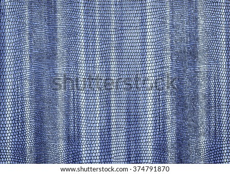 Snakeskin print curtain in pale blue for use as a background or texture - stock photo
