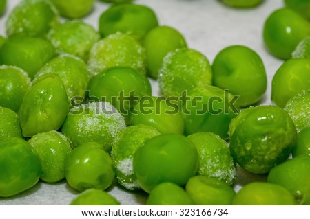 Snap-frozen peas, out of the freezer, during the thawing process. - stock photo