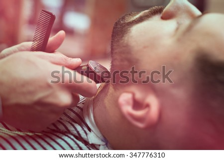Snapshot haircut beard electric typewriter. Customer shear beard in the men's barber shop. - stock photo