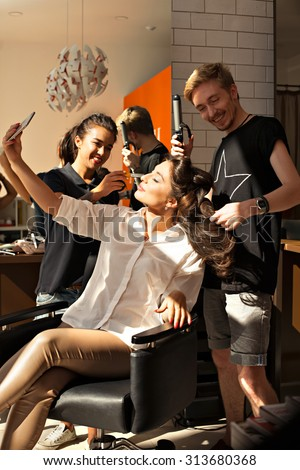 Snapshot satisfied customer of a beauty salon. Hairdresser and make-up artist at work on the image of a young beautiful girl. Make-up artist doing make-up, hairdresser makes hair styling- stock photo. - stock photo