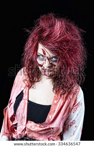 Snarling, red-headed zombie girl in bloody, tattered clothing.  Shot on black background.