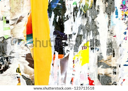 snatches of old ads and posters on a concrete wall - stock photo