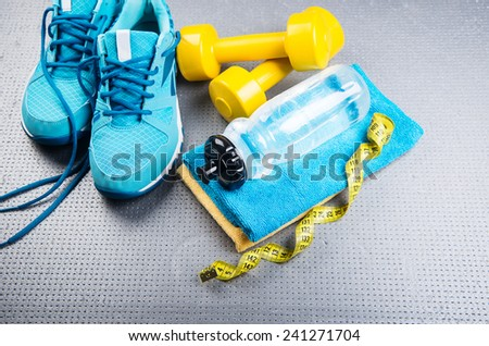 Sneakers and dumbbells fitness on a gray background. Different tools for sport - stock photo