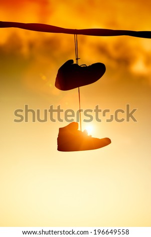 Sneakers hanging from a cable - stock photo