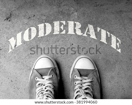 Sneakers on concrete floor background with text : Moderate