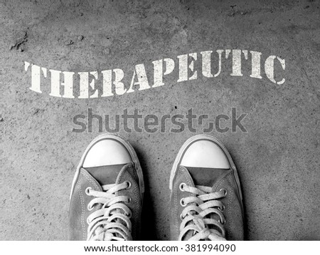 Sneakers on concrete floor background with text : Therapeutic