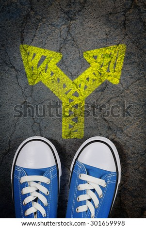 sneakers on cracked concrete surface with painted arrow pointing in two different directions - stock photo