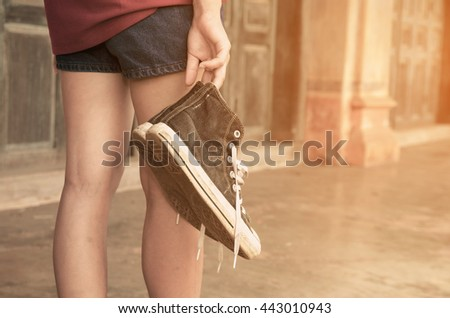 sneakers on hand woman.Outdoor lifestyle close-up of the legs of black beautiful teenage girl.