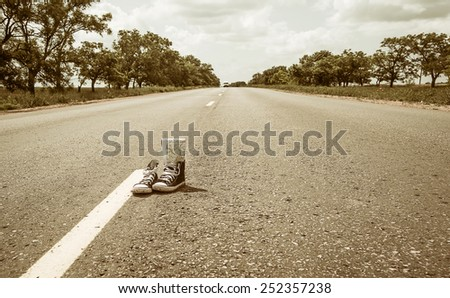sneakers on the road. road. journey - stock photo