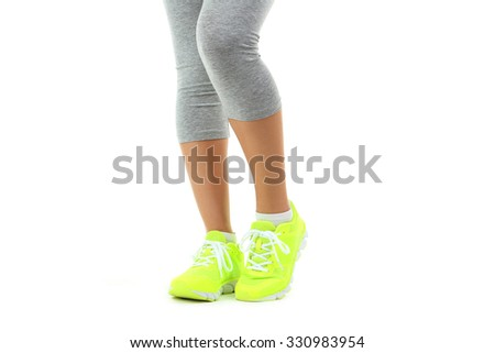 Sneakers on women legs on a white background - stock photo