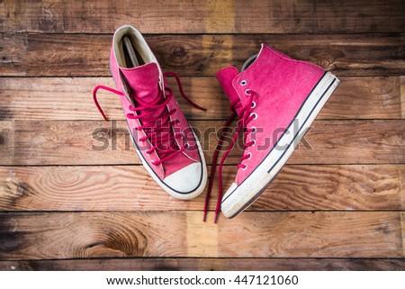 Sneakers on wooden floor - stock photo