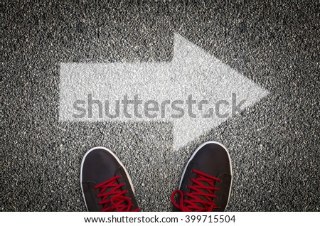 Sneakers standing on a road with arrow - stock photo