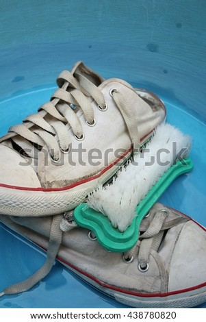 Sneakers wash enameled bowl with soapy water. - stock photo